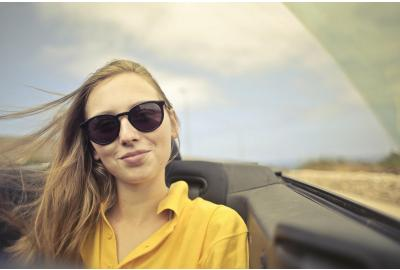 woman_in_sunglassses_and_a_yellow_shirt_sitting_in_the_passener_seat_of_a_car