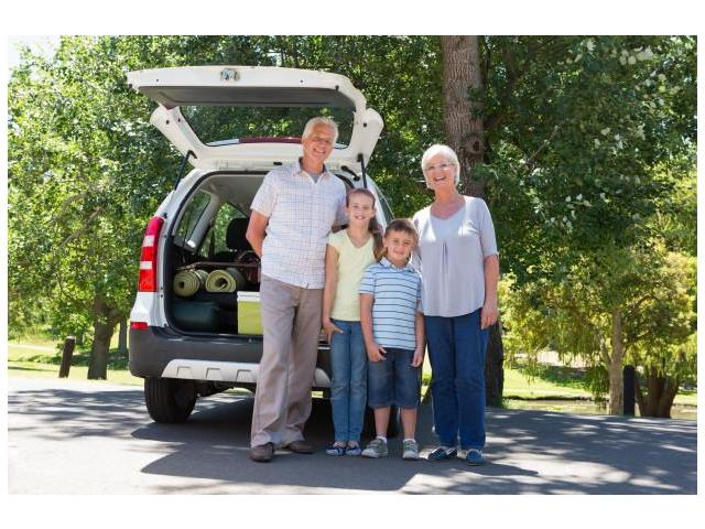 family_standing_infront_of_the_back_of_an_SUV_with_an_open_boot