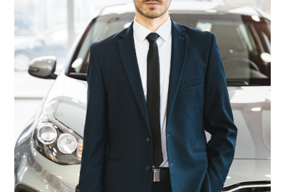 man_standing_in_front_of_a_car_in_a_dealership