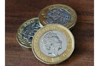 pound_coins_on_a_wood_surface
