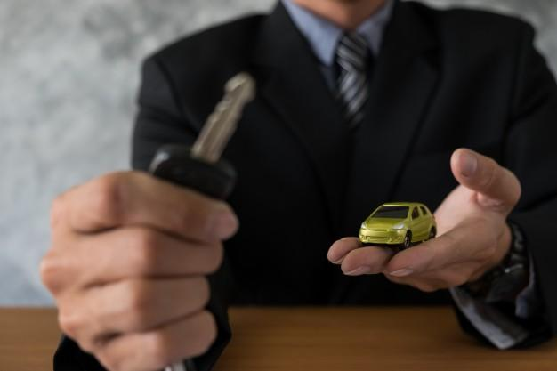 image of a man holding a key and a model car